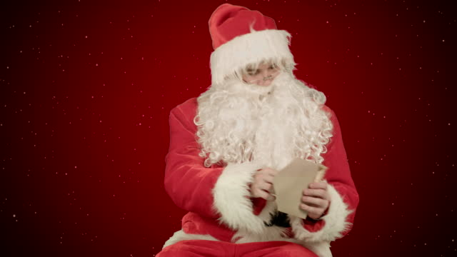Santa-with-Christmas-letter-or-wish-list-on-red-background-with-snow