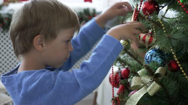Little-boy-decorates-the-Christmas-tree-