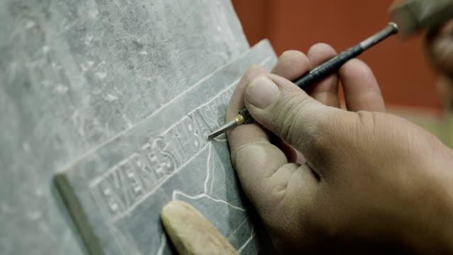 Nepalese-craftsman-working-on-traditional-Mani-slate-stone-in-Kathmandu-Nepal-
