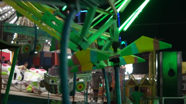 Carnival-with-ferris-wheel-bright-colourful-lights-car-carousel-at-night-closeup