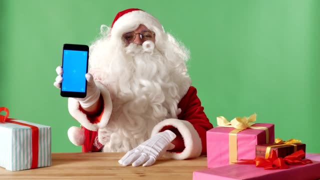 Smiling-Santa-Claus-showing-smartphone-in-camera-gifts-on-the-table-chromakey-in-the-background