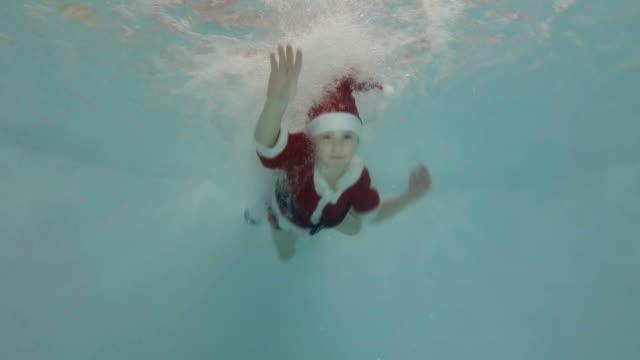 Niño-feliz-en-un-traje-rojo-de-Santa-Claus-se-presenta-bajo-el-agua-en-la-piscina-jugando-en-los-chorros-de-agua-sonriendo-y-mirando-a-la-cámara-