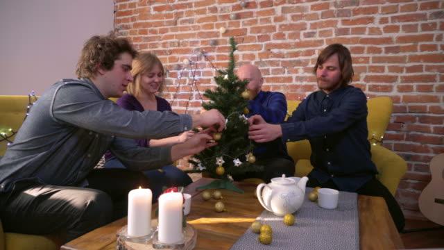 Amigos-adornar-arbolito-de-Navidad