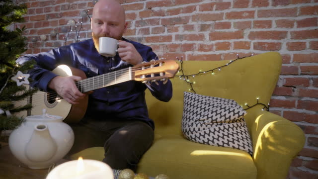 Hombre-bebiendo-té-y-tocar-la-guitarra-junto-al-árbol-de-Navidad