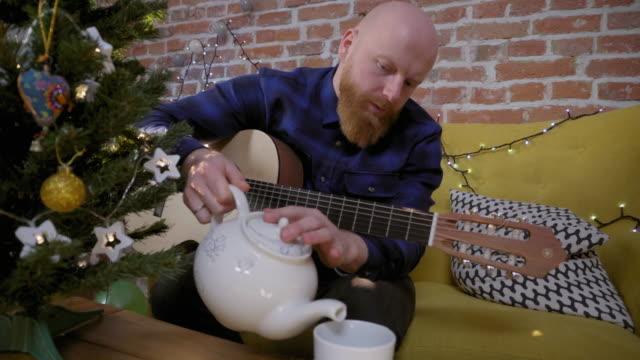 Hombre-con-guitarra-sentado-junto-al-árbol-de-Navidad-y-vertiendo-té