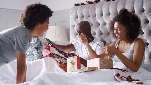 Young-mixed-race-family-unwrapping-presents-in-bed-on-Christmas-morning-smiling-and-hugging-each-other-close-up