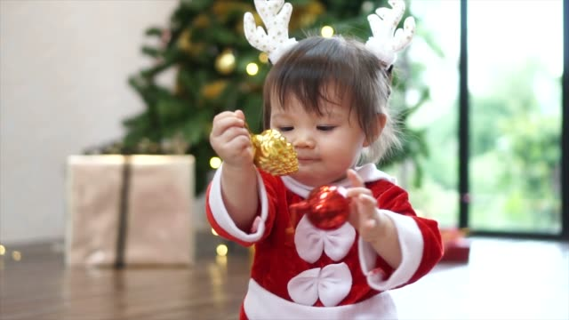 Cute-1-year-old-baby-girl-wearing-reindeer-headband-playing-with-Christmas-ornament-with-christmas-tree-in-background-Merry-Christmas-and-Happy-Holidays-