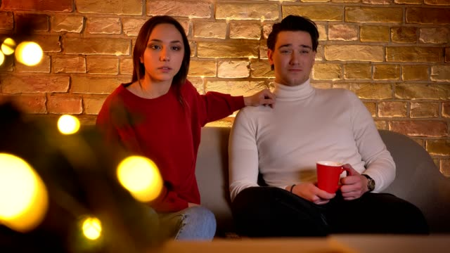 Embracing-caucasian-couple-sitting-on-sofa-and-attentively-watching-movie-with-cup-of-beverage-in-christmas-atmosphere-