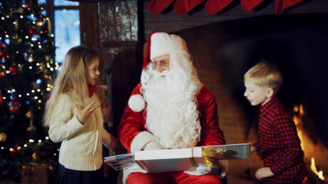 Santa-Claus-is-sitting-in-the-middle-of-a-room-with-an-album-in-his-hands-surrounded-by-children-on-the-background-of-a-fireplace-and-telling-a-New-Year-story-