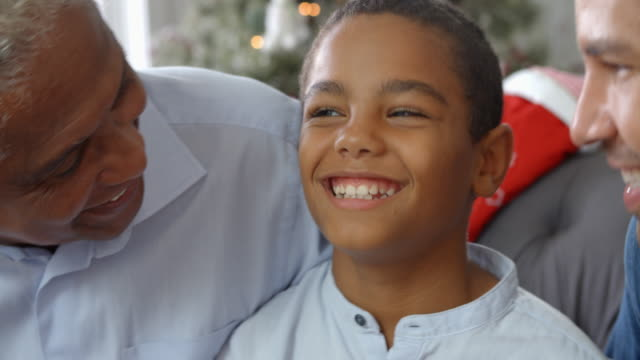 Close-Up-Of-Boy-With-Grandfather-And-Father-At-Christmas