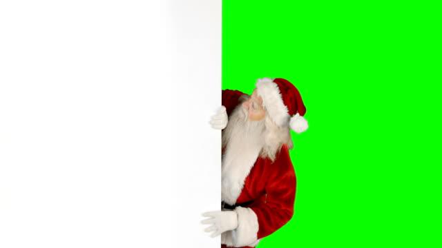 Santa-claus-hiding-behind-green-screen
