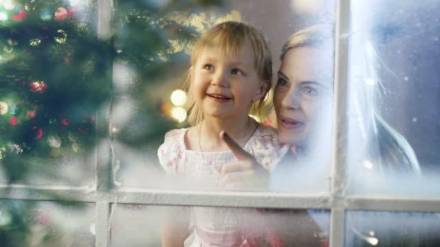 En-Nochebuena-madre-e-hija-mirando-a-través-de-la-ventana-Nevada-Guirnalda-brilla-brillante-en-una-ventana-