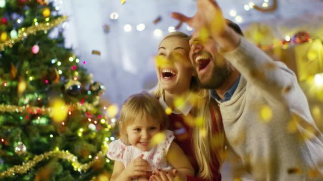 En-Nochebuena-padre-madre-y-su-hijita-tienen-buen-tiempo-celebrando-con-el-rodaje-de-confeti-