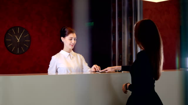 Service-manager-at-hotel-lobby-meets-visitor-4K-