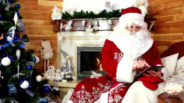 santa-claus-using-tablet-saint-nicholas-surfing-internet-with-tablet-pc-digital-device-christmas