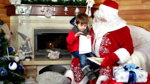 little-boy-open-his-christmas-letter-child-sitting-on-santas-lap-kid-visit-saint-nicolas-residence