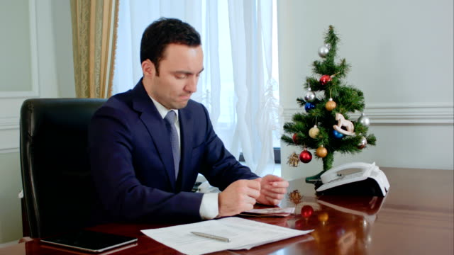 Disappointed-young-businessman-counts-money-before-Christmas