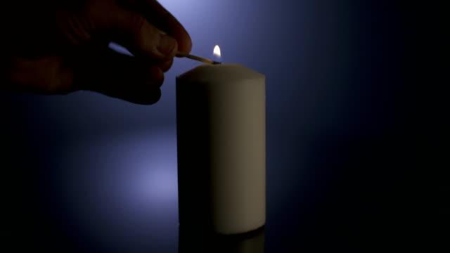 Imágenes-de-macro-lenta-de-una-vela-blanca-encienden-por-un-partido-sobre-un-fondo-oscuro