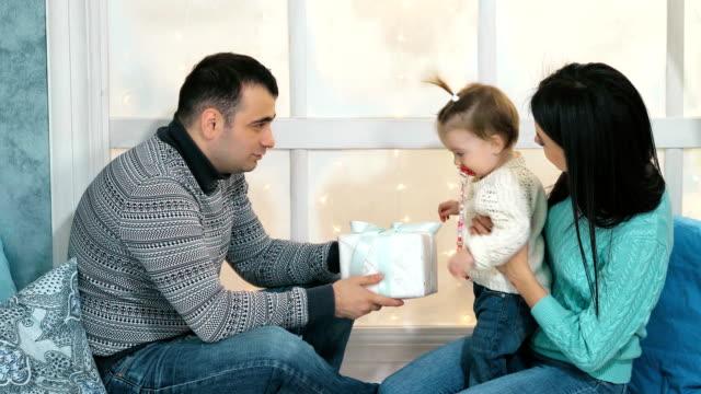 Hermosa-familia-feliz-Navidad-con-niña-en-suéteres-de-punto-sentado-en-el-alféizar-de-la-ventana