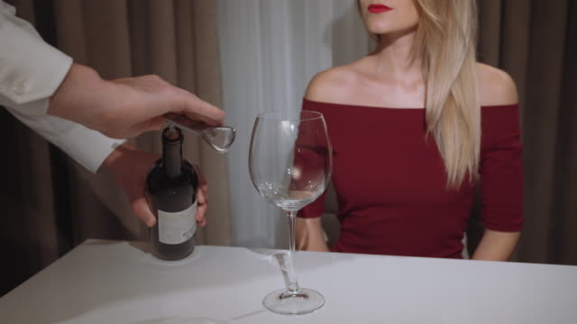 waiter-opens-a-bottle-of-red-wine-for-a-woman-in-a-restaurant