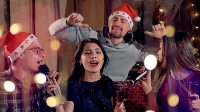 Group-of-joyfull-friends-singing-karaoke-having-fun-at-Christmas-party-4K-