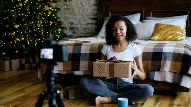Young-curly-mixed-race-woman-recording-video-blog-about-packing-christmas-gift-box-at-home