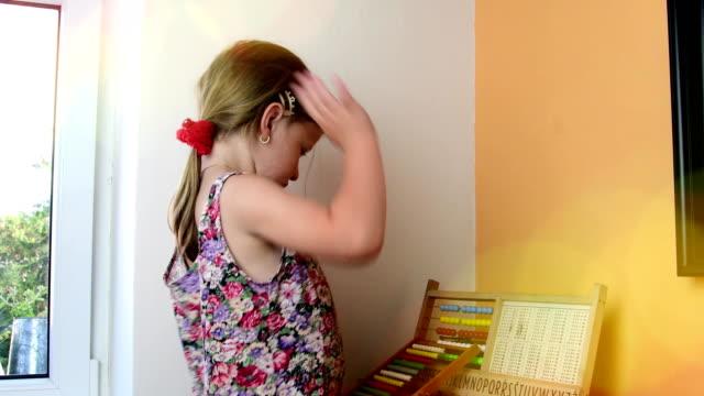 Süßes-kleines-Mädchen-spielt-mit-Abakus-und-schreibt-an-die-Tafel-mit-Kreide-Vorschule-Konzept-Kindheit-Spielzeug-Abakus-mit-tschechischen-Alphabet-Nettes-Mädchen-wie-Vorschulkind-Bokeh-Unschärfe