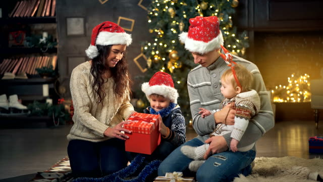 Familia-abrir-regalo-frente-a-árbol-de-Navidad