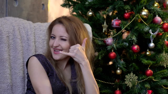 attractive-happy-girl-gesturing-with-fingers-call-me-on-christmas-tree-background
