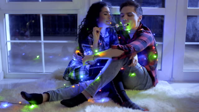 Beautiful-couple-decorated-with-christmas-garland-eats-marshmellows