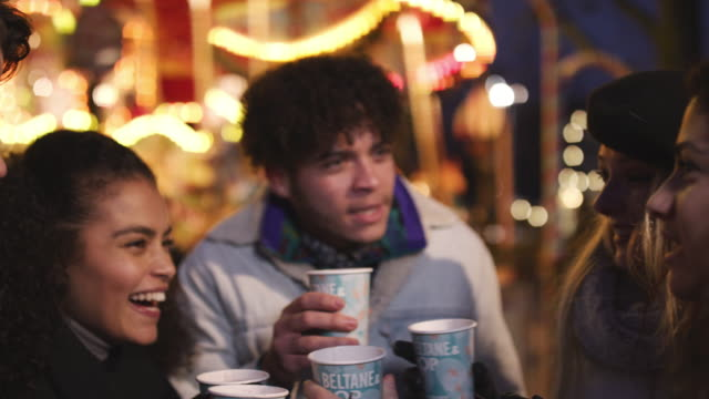 Group-Of-Friends-Drinking-Mulled-Wine-At-Christmas-Market
