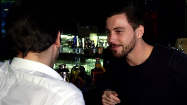Junge-männliche-Freunde-reden-während-zusammen-die-Getränke-an-der-bar