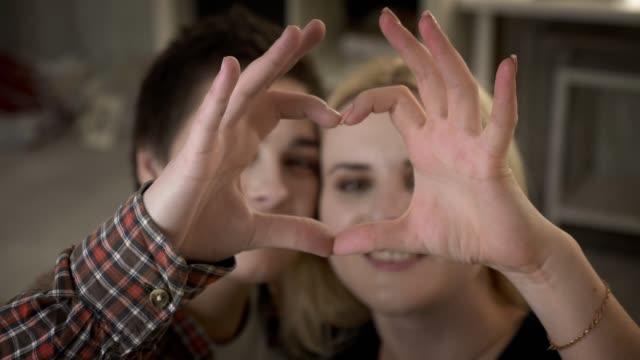 Zwei-süße-lesbische-Mädchen-kuscheln-und-zeigen-die-Zeichen-des-Herzens-das-Zeichen-der-Liebe-Familie-60-fps