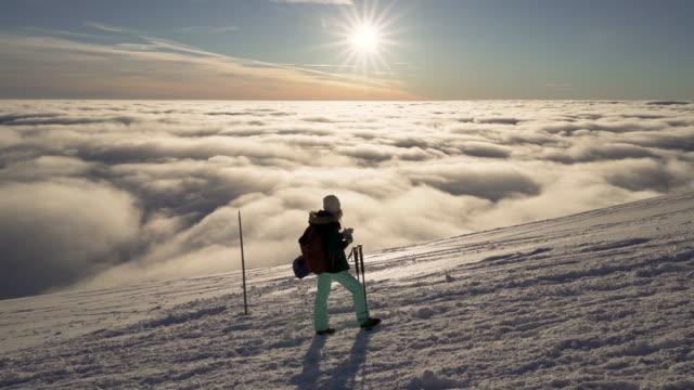 Stabilisierte-Fluss-Bewegungsaufnahme-des-Mädchens-Wandern-auf-Schnee-im-slowakischen-Gebirge-über-Wolken-bei-Sonnenuntergang-im-winter