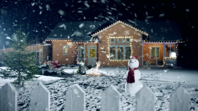 Footage-of-the-Idyllic-House-Decorated-with-Garlands-on-Christmas-Eve-Snowman-and-Christmas-Tree-stand-on-the-Front-Yard-Beautiful-Winter-Evening-with-Falling-Soft-Snow-