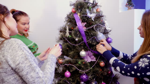 Three-girls-decorating-a-Christmas-tree-and-talking