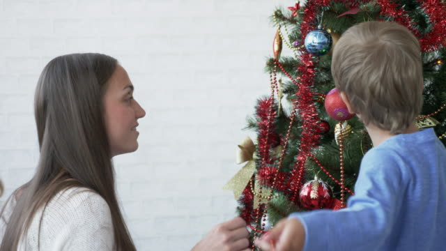 Family-of-mother-and-two-kids-around-a-Christmas-tree-to-decorate-it