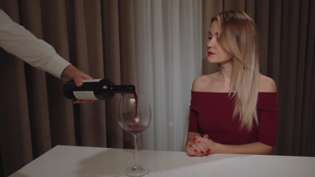 the-waiter-pours-red-wine-for-a-beautiful-young-woman-with-red-lipstick-in-a-restaurant