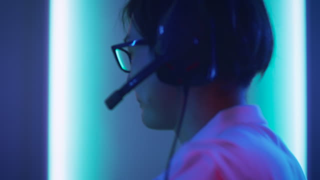 Close-up-Portrait-Shot-of-the-Professional-East-Asian-Gamer-Playing-in-Online-Video-Game-on-His-Personal-Computer-Talking-into-Microphone-Room-Lit-by-Neon-Lights-in-Retro-Arcade-Style-Cyber-Sport-Championship-