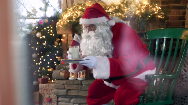Tired-santa-claus-eating-cookies-and-drinking-milk