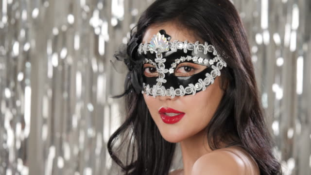 Sexy-woman-wearing-masquerade-mask-flirting-at-party-over-silver-glitter-background-slow-motion
