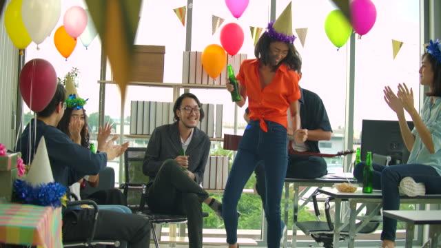 Equipo-de-gente-joven-bailando-y-haber-divertido-celebrar-con-pan-tostado-y-tintineo-levantando-copas-en-su-oficina-Lenta-de-disparo