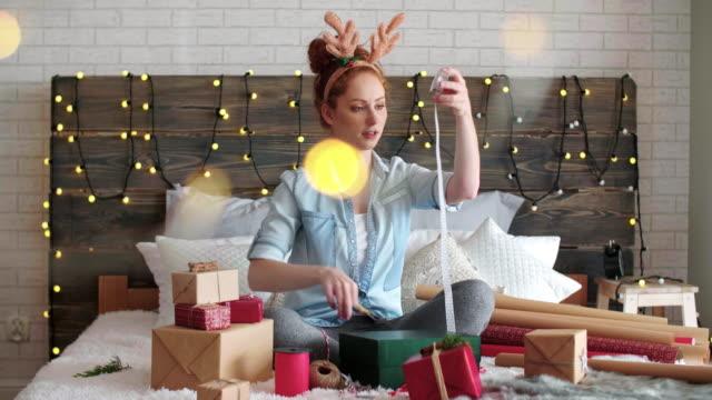 Chica-feliz-envolviendo-los-regalos-de-Navidad-en-la-cama