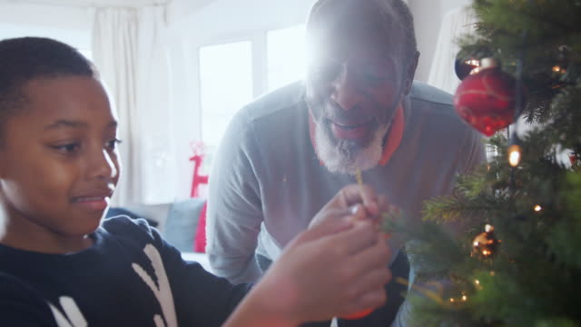 Grandfather-And-Grandson-Hanging-Decorations-On-Christmas-Tree-At-Home-Together