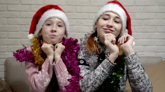 Two-happy-girls-in-Santa-hats-and-tinsel-on-their-shoulders-smile-and-dance-sitting-at-a-table-against-a-white-wall-Portrait-