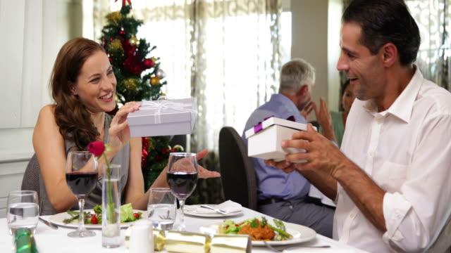 Glückliches-Paar-mit-einem-Weihnachts-Essen-zusammen-und-den-Austausch-von-Geschenken