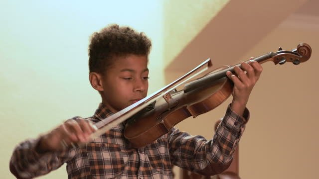 Smiling-afro-kid-plays-on-violin-