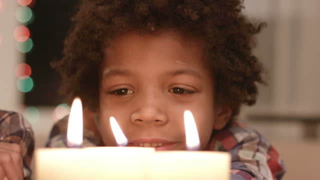 Smiling-boy-looks-at-candle-