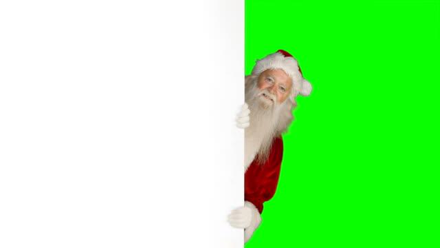 Überrascht-Weihnachtsmann-versteckt-sich-hinter-weißen-Bildschirm