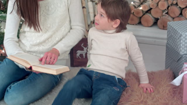 Capricious-boy-listening-to-his-mom-reading-a-book-near-Christmas-tree